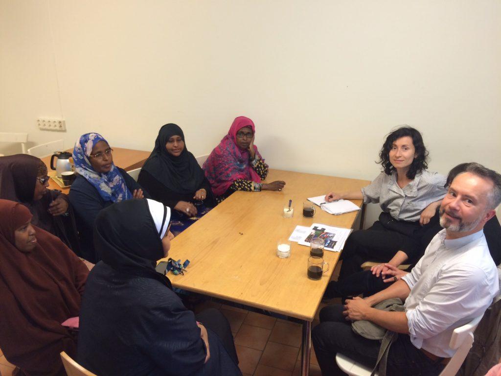 En grupp kvinnor i sjal vid ett bord tillsammans med Statens konstråds projektledare. Hammarkullen, Konst händer.