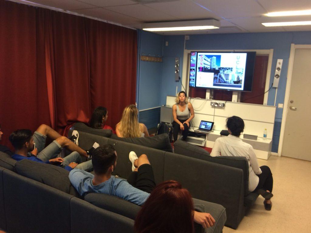 Konstnären Roxy Farhat sitter vid en teveskärm och talar med en grupp ungdomar.