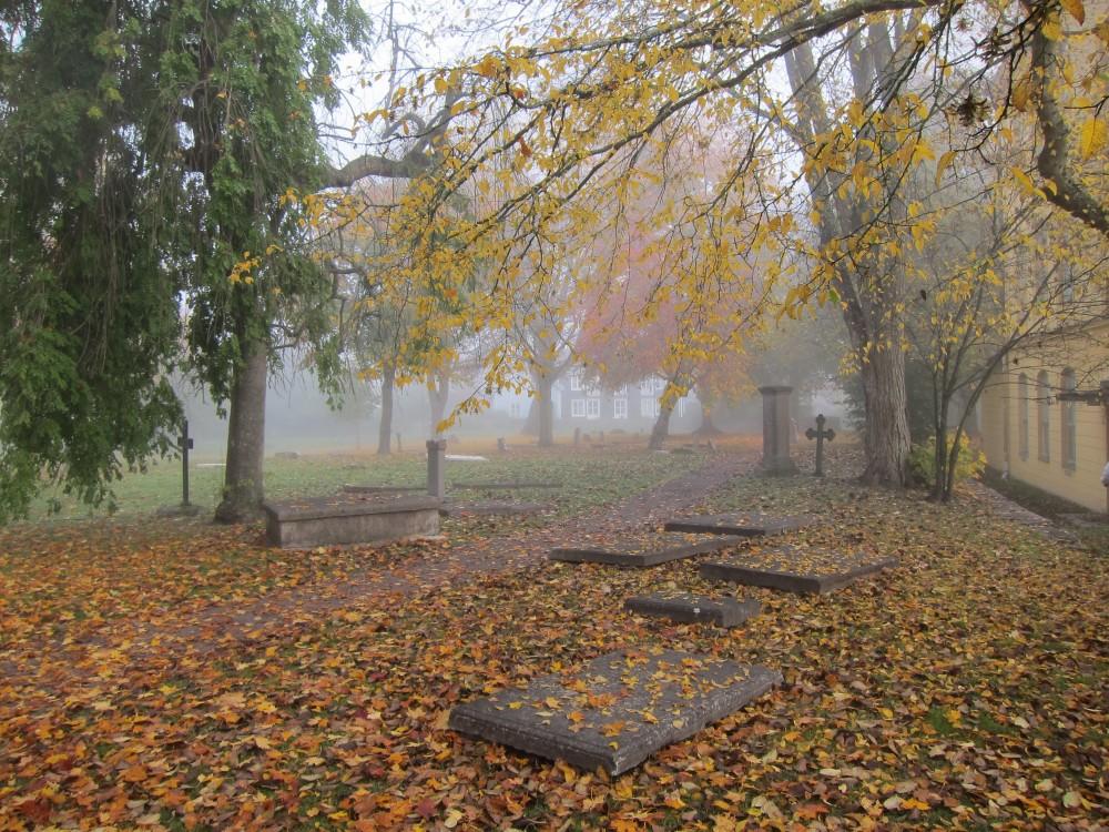 En dimmig höstdag på Gamla kyrkogården i Kalmar. Gula löv ligger spridda över gravstenarna. Pia Sandström, Minnet Orden Marken...