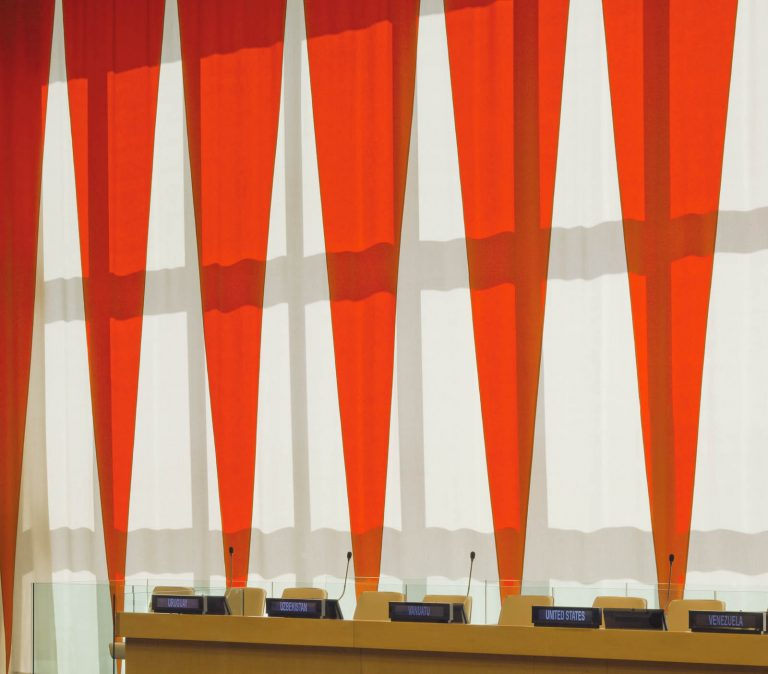 Ridå av uppåtriktade vita och nedåtriktade röda trianglar, med talarstol framför. Ann Edholm, Dialogos, 2013