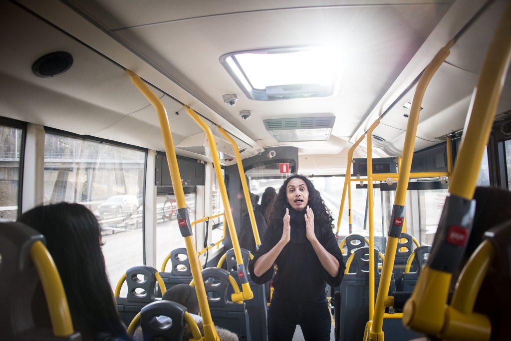 En kvinna står och pratar i mittgången på en buss.