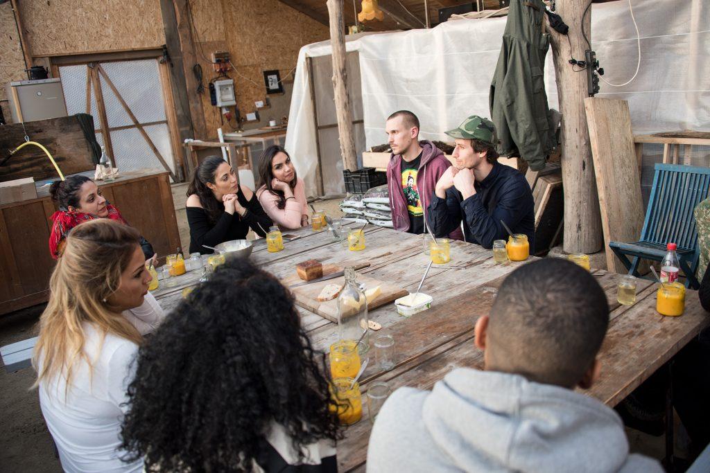 Fem kvinnor och tre män fikar vid ett fyrkantigt träbord.
