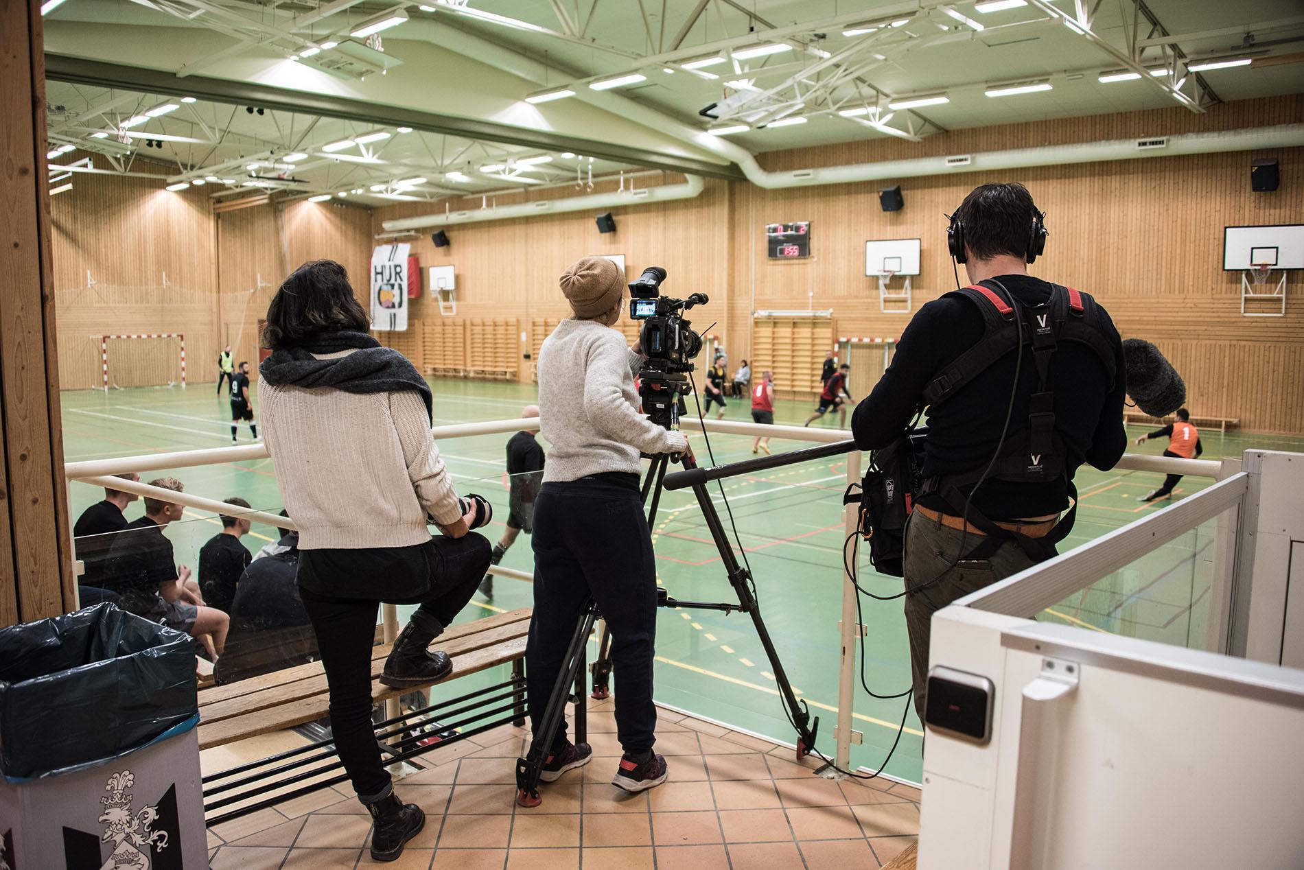 Ett filmteam på tre personer dokumenterar en fotbollsmatch.