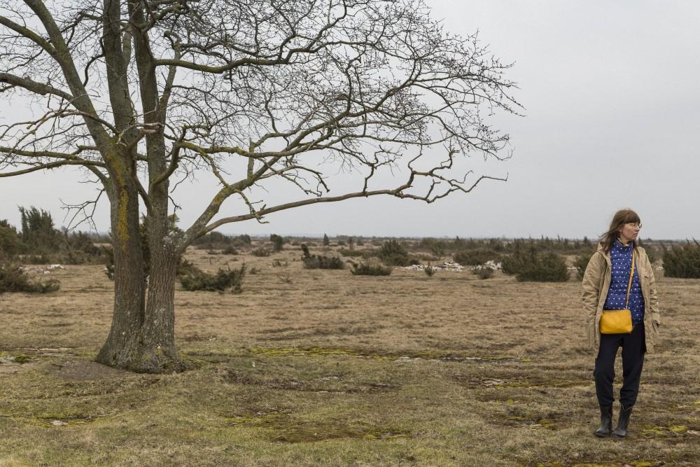En kvinna står vid ett träd i Dröstorp Naturreservat på Öland. I bakgrunden gräs och låga buskar. Pia Sandström, Minnet Orden Marken...