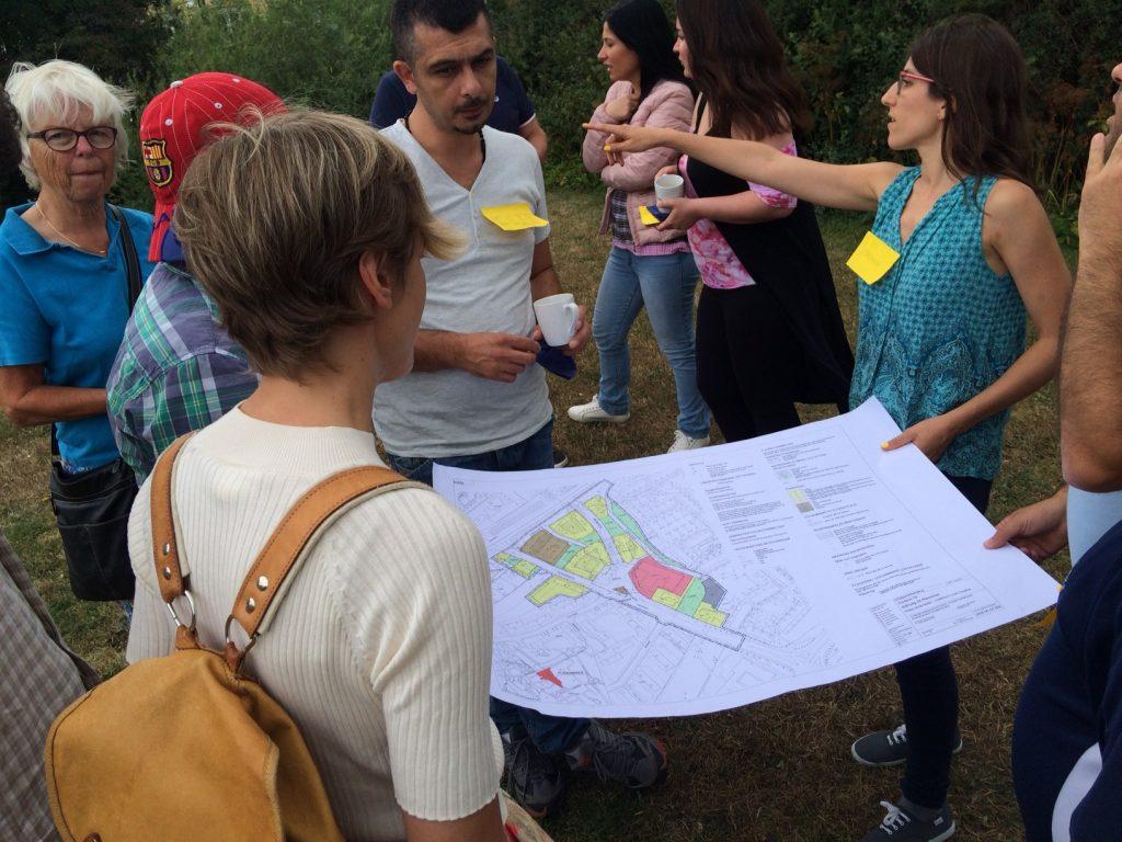 Åtta personer står samlade runt en områdeskarta. En kvinna pekar och instruerar. Hageby, Norrköping, Konst händer
