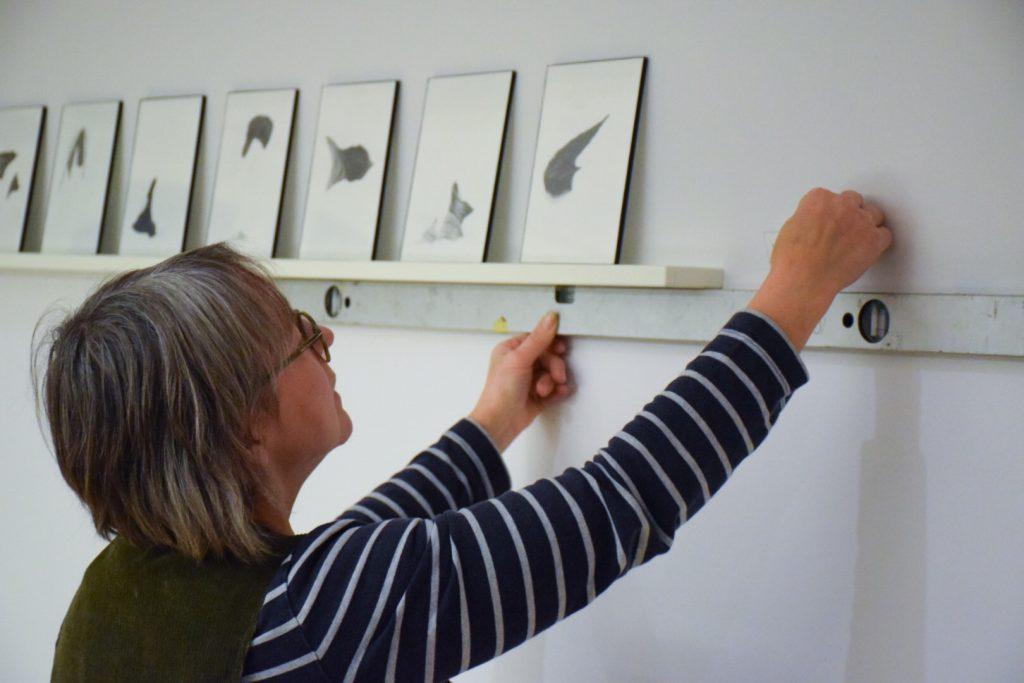 Konstkonsult Birgitta Silfverhielm mäter med vattenpass hur tavlorna ska sitta. Dokumentation, Konstkollektion Stockholms Akademiska Forum