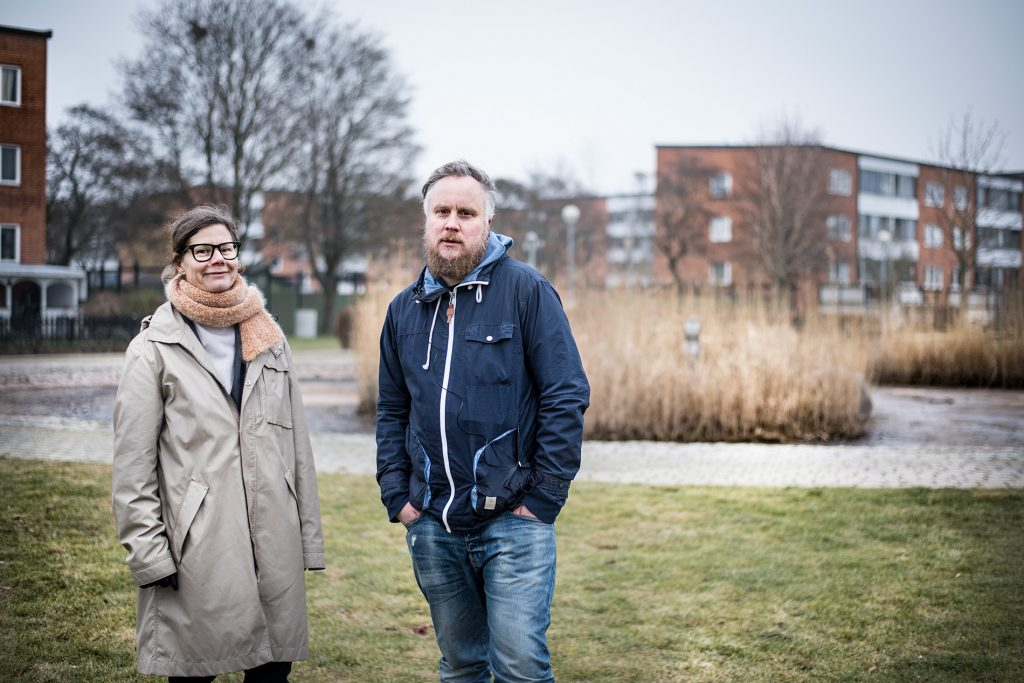 En kvinna och en man står i ett bostadsområde.
