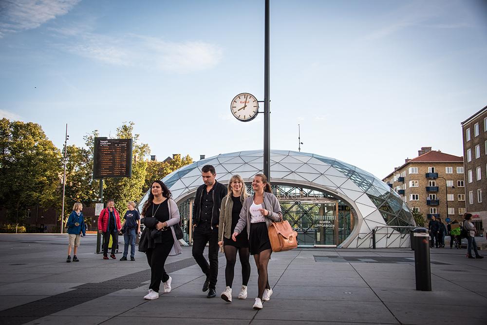 """En grupp människor lämnar den glasöverbyggda utgången från station Triangeln. Ovanför deras huvuden ser man en vanlig offentlig klocka med texten """"Kabul"""" i rött. Jens Haaning, Kabul Time."""
