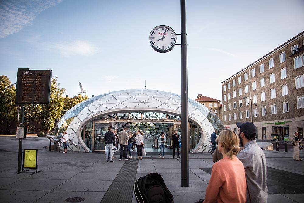 """Folk går in och ut i den glasöverbyggda entrén till station Triangeln. Ovanför deras huvuden ser man en vanlig offentlig klocka med texten """"Kabul"""" i rött. Jens Haaning, Kabul Time."""
