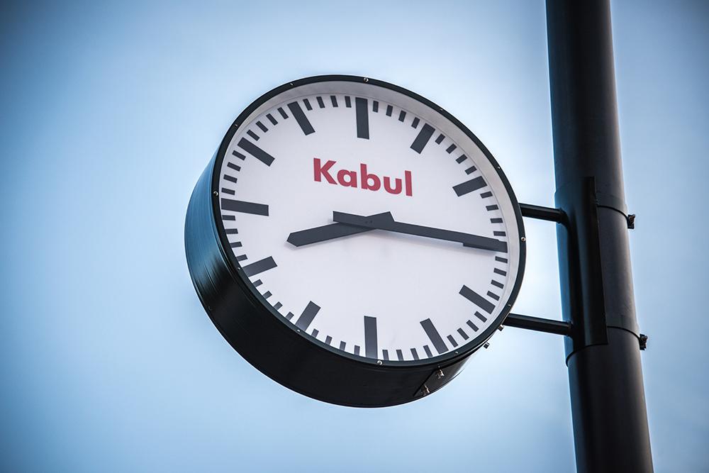 """Offentlig klocka på en svart pelare. Visarna pekar på åtta och femton. I urtavlan står den röda texten: """"Kabul"""". Jens Haaning, Kabul Time."""
