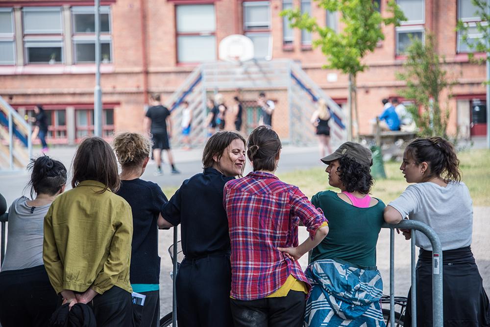 Fyra kvinnor står vid ett staket och pratar. Framför dem spelas basket på en skolgård. Myriam Lefkowitz, Walk, hands, eyes (Gamlegården)