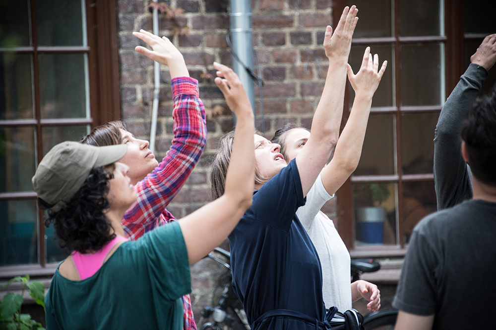 Fyra kvinnor står utomhus med höger hand lyft och blicked i handflatan. Myriam Lefkowitz, Walk, hands, eyes (Gamlegården)