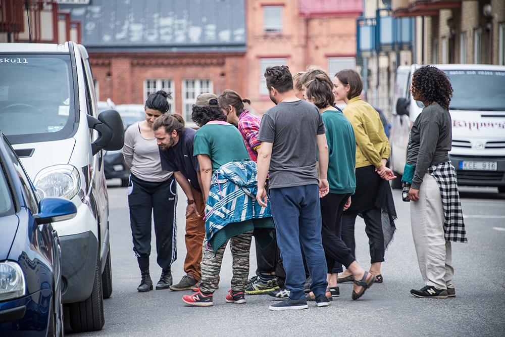 Tio personer står i en klunga på gatan och studerar karossen på en parkerad bil. Myriam Lefkowitz, Walk, hands, eyes (Gamlegården)