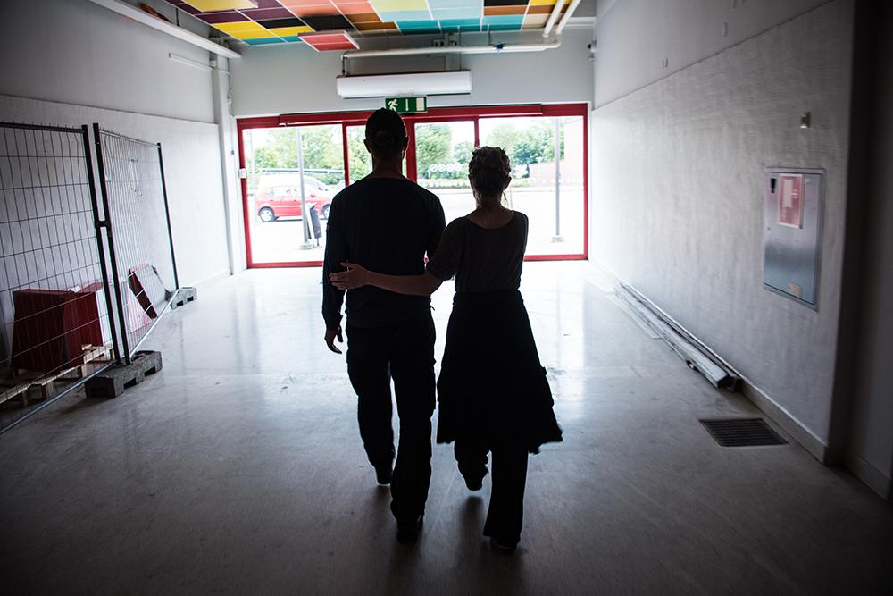 En man och en kvinna går bort från kameran mot en utgång. Kvinnan leder mannen genom att hålla med ena handen i hans vänstra armbåge och med den andra i hans högra underarm. Myriam Lefkowitz, Walk, hands, eyes (Gamlegården)