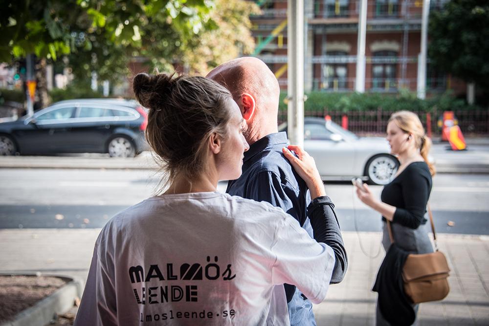 En kvinna i vit t-tröja står med ryggen mot kameran. Hon guidar en man som står framför henne, halvt dold för kameran. Myriam Lefkowitz, Walk, Hands, Eyes (Malmö)