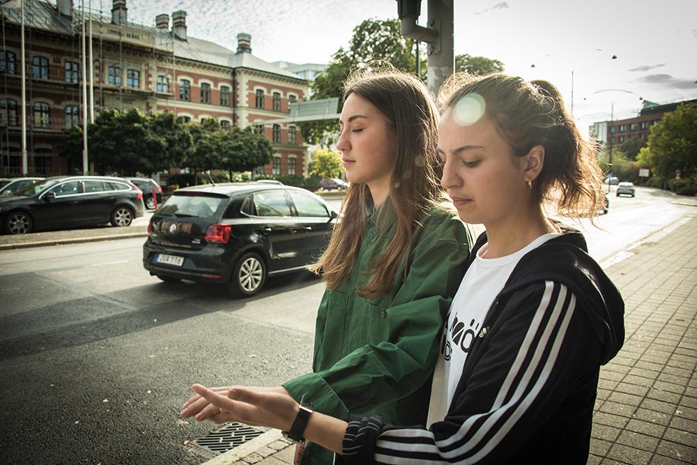 En kvinna med slutna ögon leds vid handen längs trottoaren av en annan kvinna. Bredvid dem kör bilar. Myriam Lefkowitz, Walk, Hands, Eyes (Malmö)