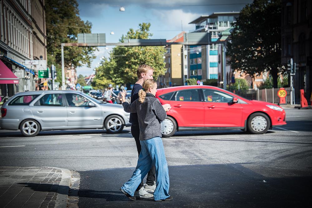 En kvinna leder en blundande man över vägen. I bakgrunden kör bilar. Myriam Lefkowitz, Walk, Hands, Eyes (Malmö)