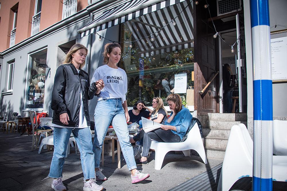 En blundande kvinna leds längs trottoaren av en annan kvinna. I bakgrunden en uteservering med människor. Myriam Lefkowitz, Walk, Hands, Eyes (Malmö)