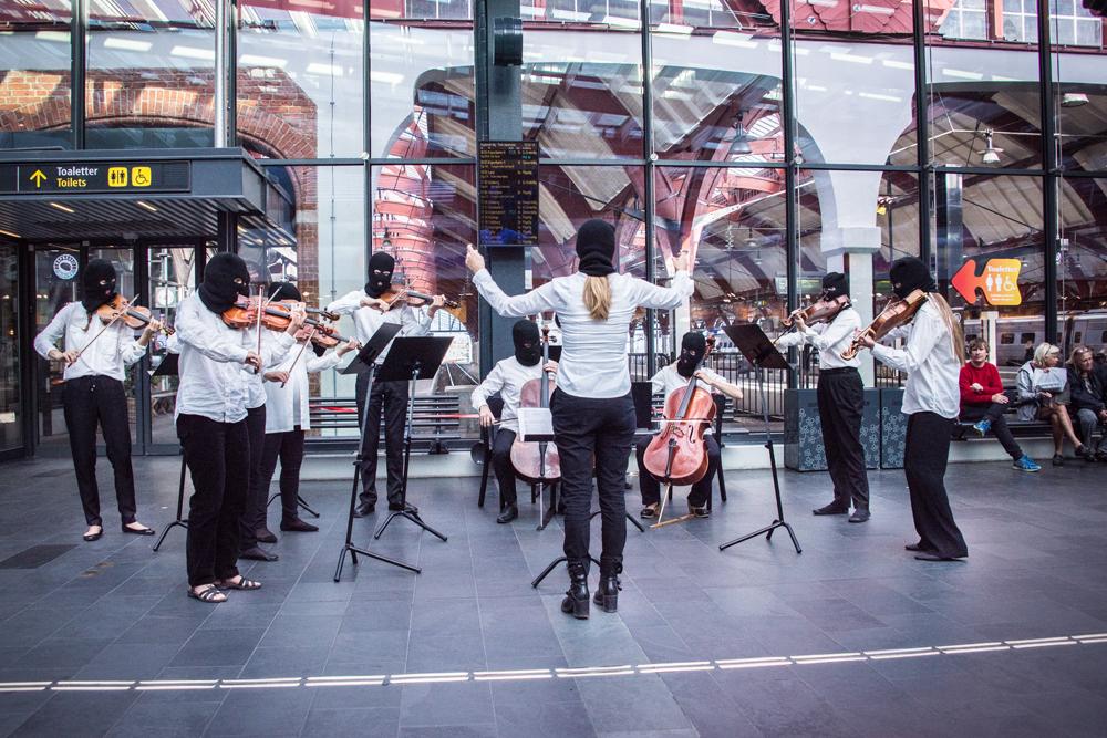 En spelande stråkensemble bestående av åtta musiker och en dirigent som har ryggen mot kameran. Alla har vita skjortor och svarta ansiktsmasker. Instrumenten är fiol, cello och viola. Sislej Xhafa, Again and again.