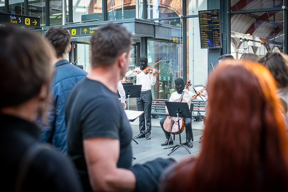 I förgrunden suddig publik som betraktar en spelande cellist och en violinist i svarta ansiktsmasker. I bakgrunden avgångstavlor för tågen. Sislej Xhafa, Again and again.