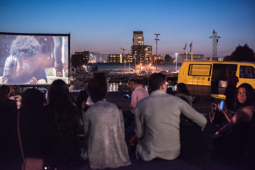 Nattbild. Publik på en utomhusbio. I bakgrunden upplysta höghus. Sunshine Socialist Cinema, Malmö´s Newsreels.