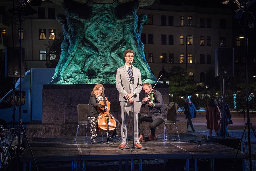 Konstnären Santiago Mostyn, iklädd slips och kostym, står på ett podium framför den upplysta statyn på Möllevångstorget. Bakom honom en cellist och en violinist. Santiago Mostyn, The repetition.