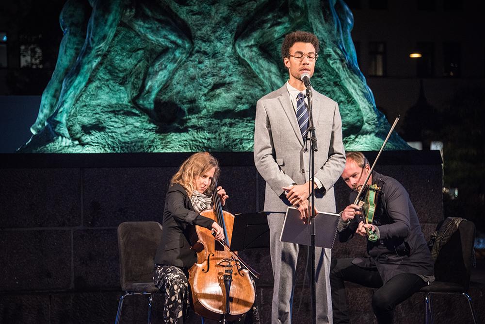 Konstnären Santiago Mostyn, iklädd slips och kostym, står på ett podium framför den upplysta statyn på Möllevångstorget. Bakom honom en cellist och en violinist. I bakgrunden torget och verket Mirakel av samme konstnär. Santiago Mostyn, The repetition och Mirakel.