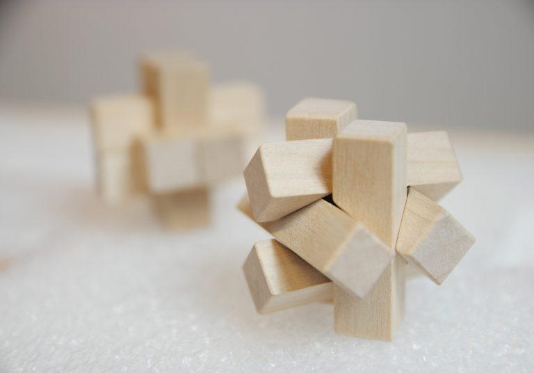 Sex små avlånga träklossar sammanlänkade till ett symmetriskt nystan. Idéförslaget Tongue and Groove.