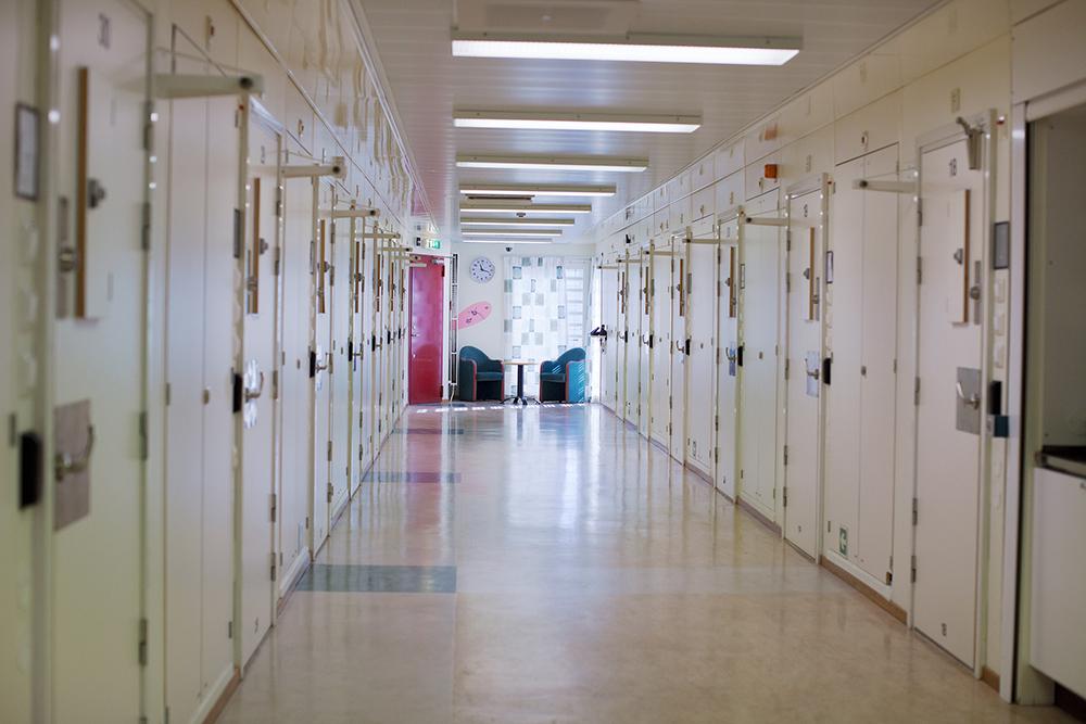 Häkteskorridor med ett femtontal bastanta dörrar på båda sidor. Längst bort en sittgrupp. Gerd Aurell, Till mitten hunnen