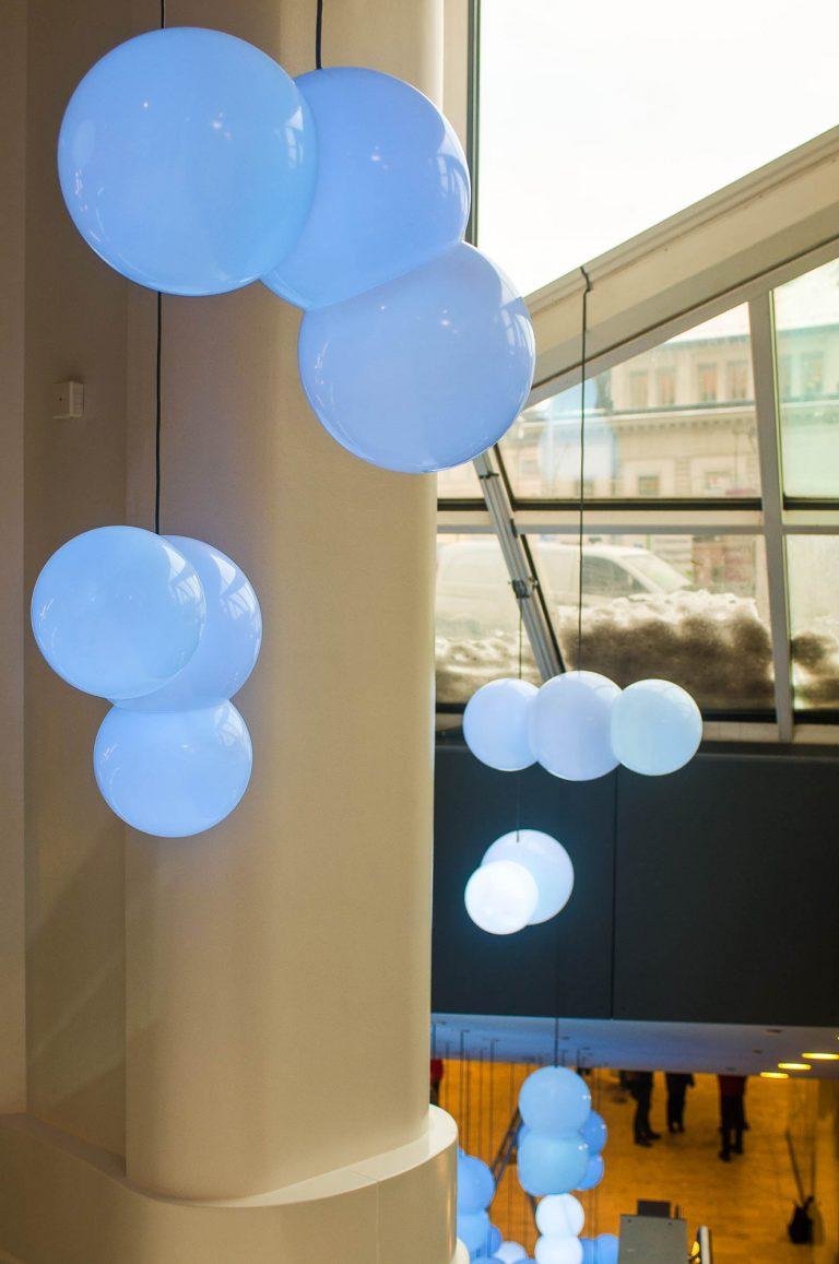 Flera kluster av klotrunda lampor i olika blå nyanser. I bakgrunden fönster mot gatan. Bigert & Bergström, Morgondagens Väder, 2012.