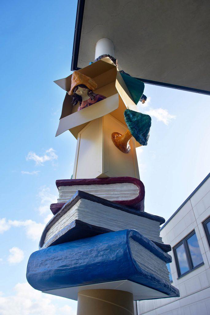 Del av skulptural pelare med tre tjocka böcker, en blå, en svart och en röd. Ovanför något som liknar en grön läslampa, som sticker ut ur sidan av ett litet skåp. Daniel Jensen, Fundamentet (2012)