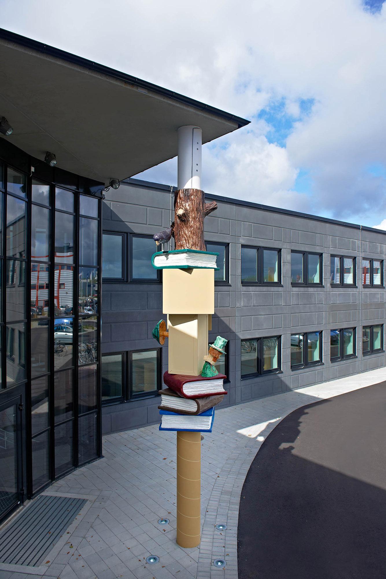 Skulptural pelare med färgglada böcker, kartonger och figurer gjutna i polyester. Daniel Jensen, Fundamentet (2012)