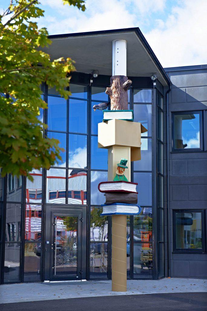 Pelaren med färgglada figurer står framför en hög glasfasad. Daniel Jensen, Fundamentet (2012)