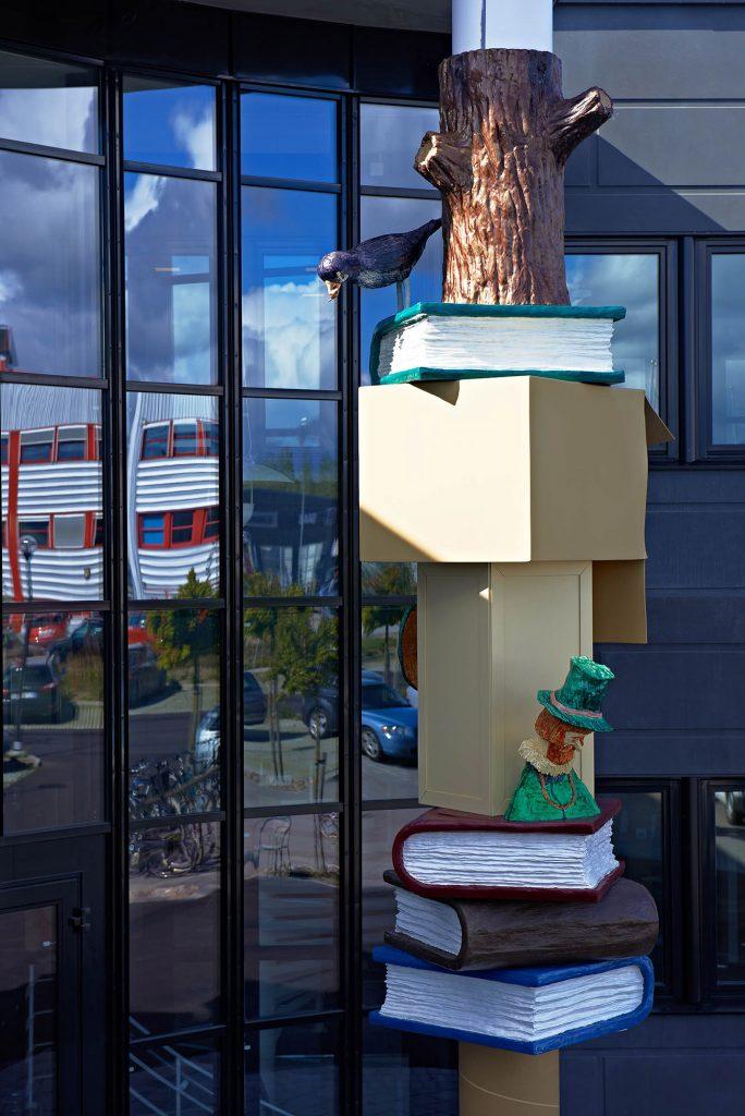 Del av pelaren med bl.a. en liten man i grön hatt och ovanför en svart fågel som kikar ner från en grön bok. Daniel Jensen, Fundamentet (2012)