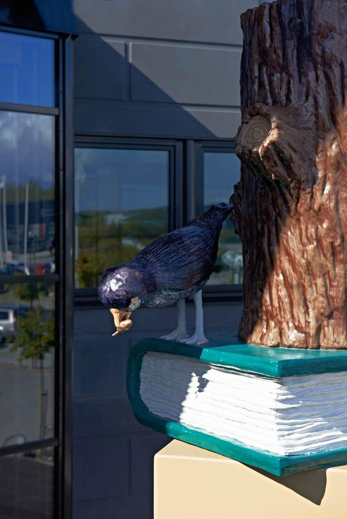 En svart fågel med något i näbben sitter bredvid en trädstam och kikar ner. Daniel Jensen, Fundamentet (2012)