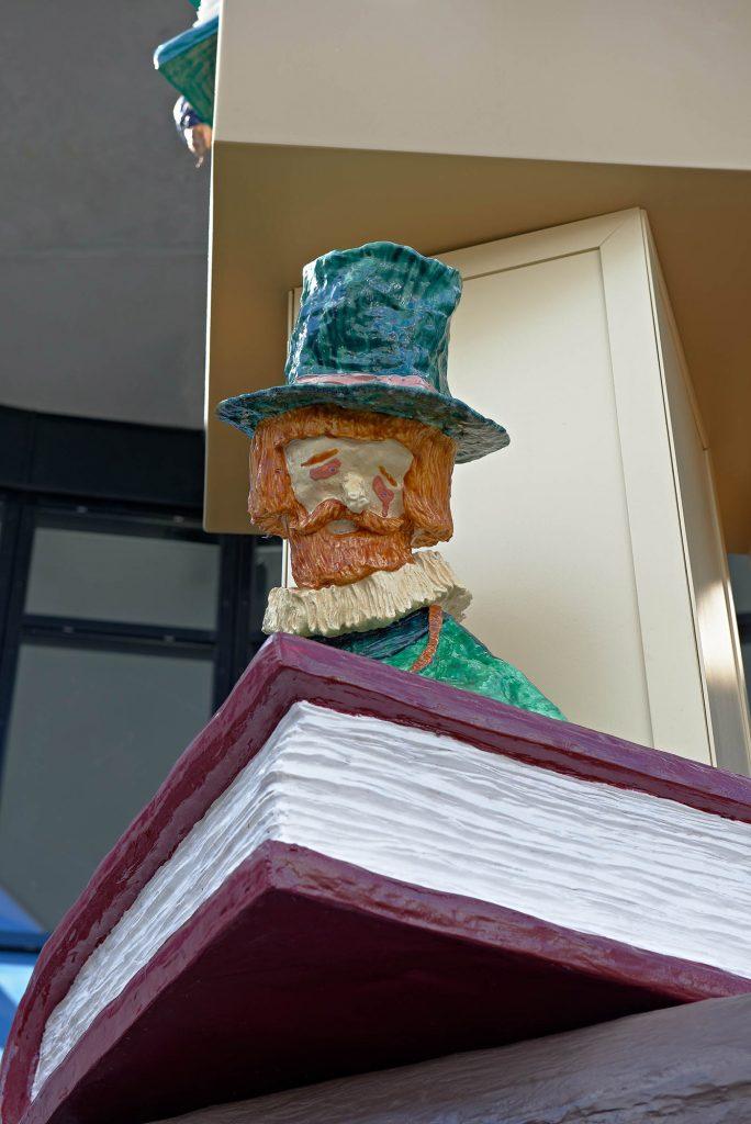 En sorgsen man i grön hatt med morotsfärgat hår och pipkrage, sitter på en stor röd bok. Del av skulptural pelare. Daniel Jensen, Fundamentet (2012)