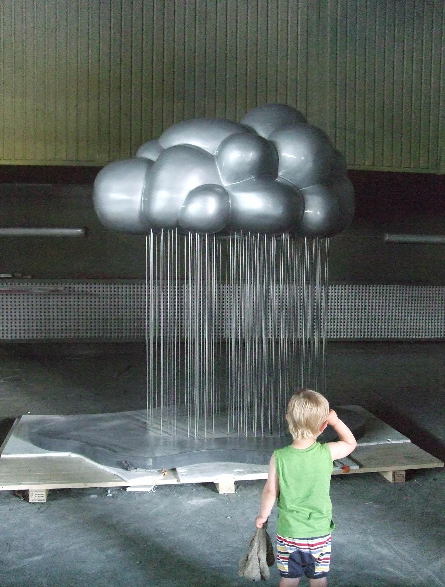 Ett barn tittar på Molnet, som är betydligt högre än barnet. Jennifer Forsberg, En liten berättelse i tre delar