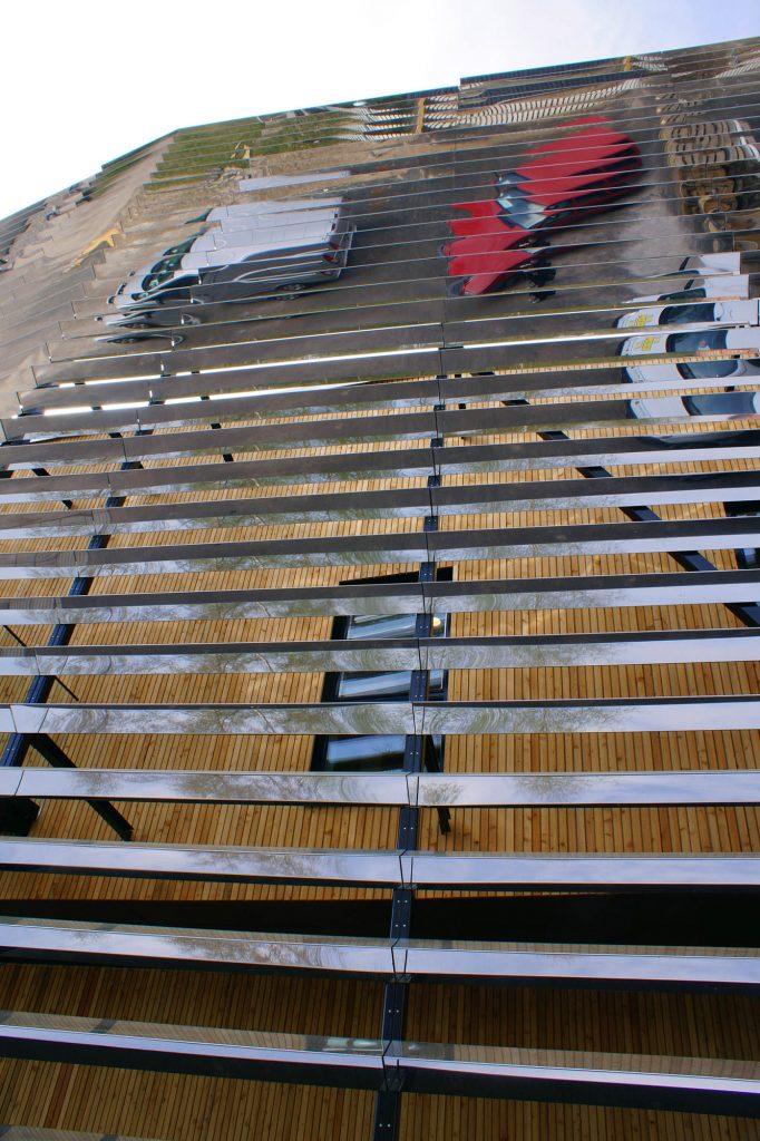 Fasaden består av längsgående prismatiska lameller i spegelblank rostfri stålplåt. Jeppe Hein, Double Reflection, 2014
