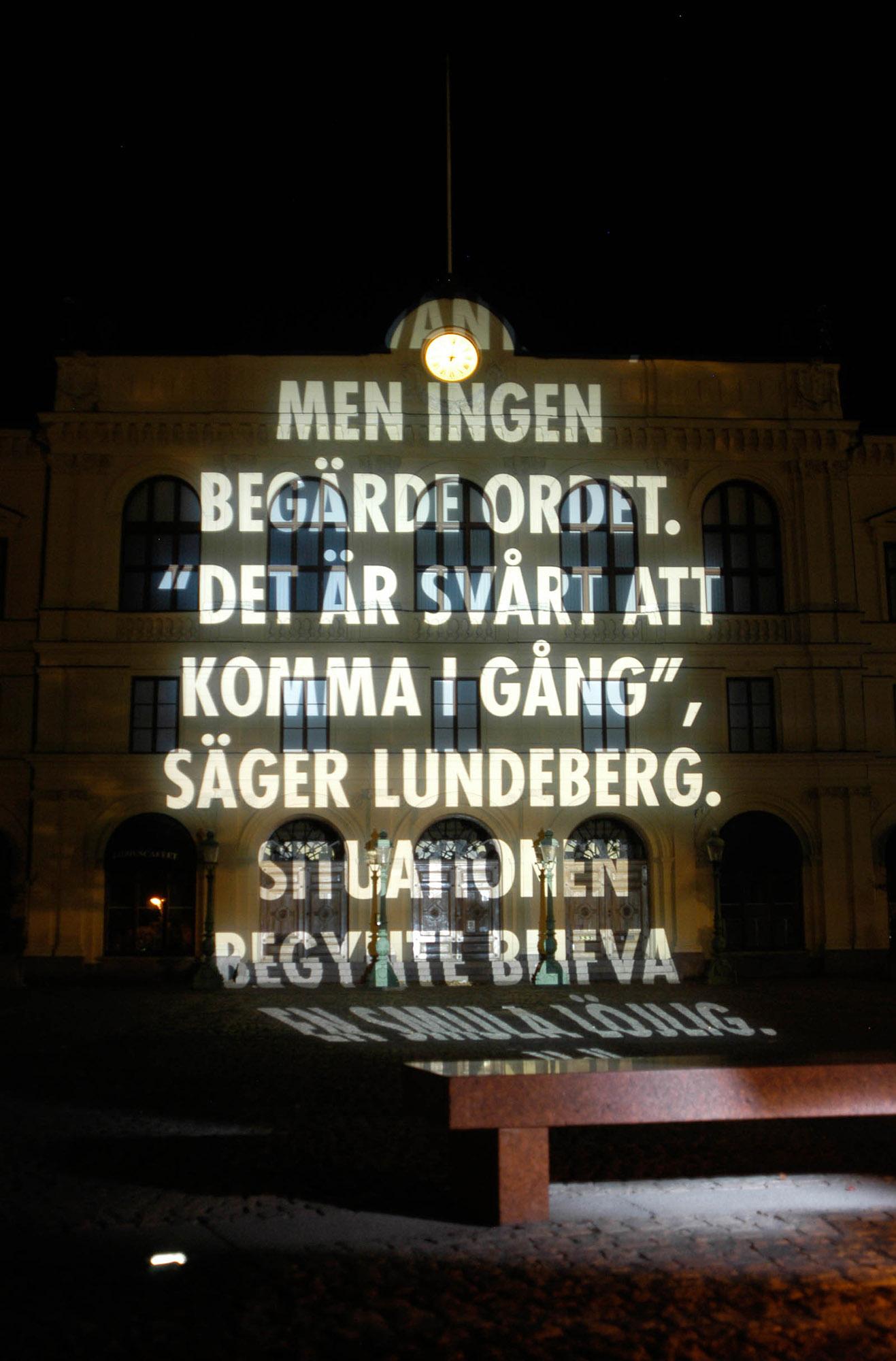 """Ljusskrift projicerad på husfasad. Det står: """"Men ingen begärde ordet. Det är svårt att komma igång säger Lundeberg. Situationen begynte blifva smått löjlig."""" Jenny Holzer, For Karlstad."""