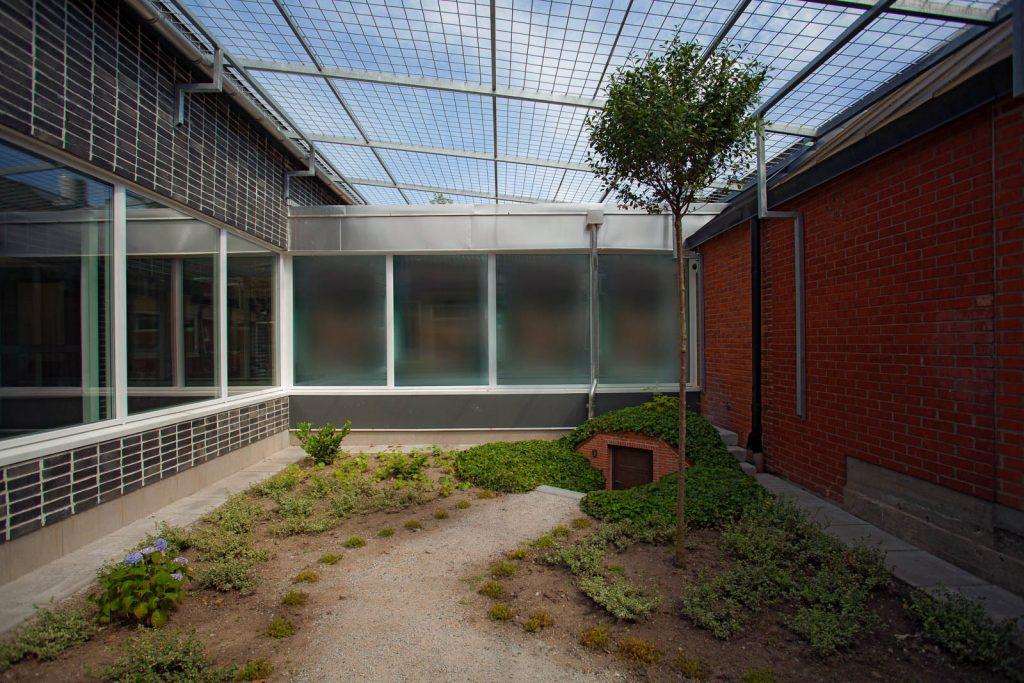 Innergård med glastak, grusgång och trappa ner till liten port. Johan Thurfjell, Egen ingång, 2014
