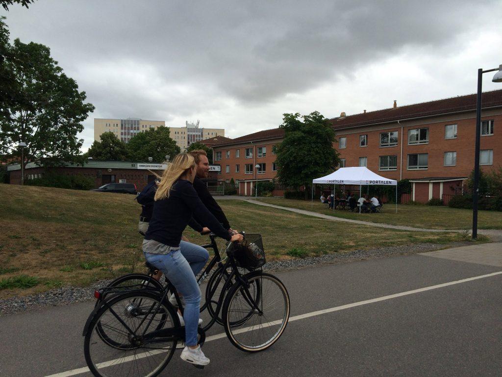 Två cyklister passerar gräsmattan med soltaket där folk sitter samlade. Hageby, Norrköping, Konst händer
