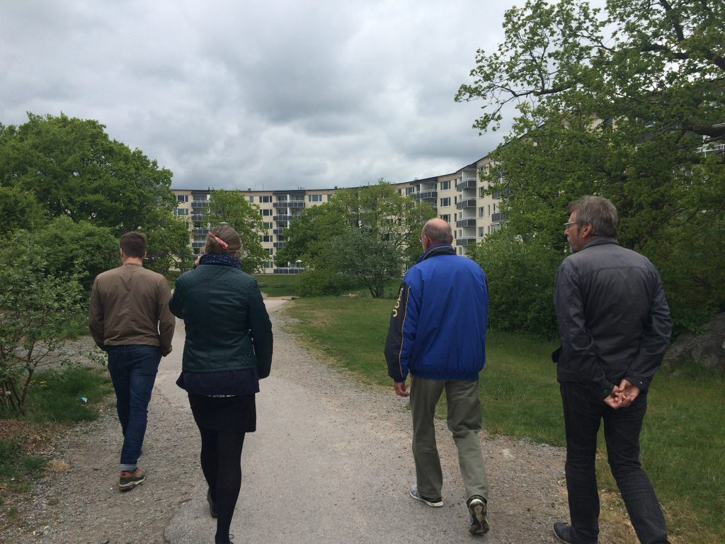 Fyra personer i ytterkläder går genom en skogsdunge i ett bostadsområde.