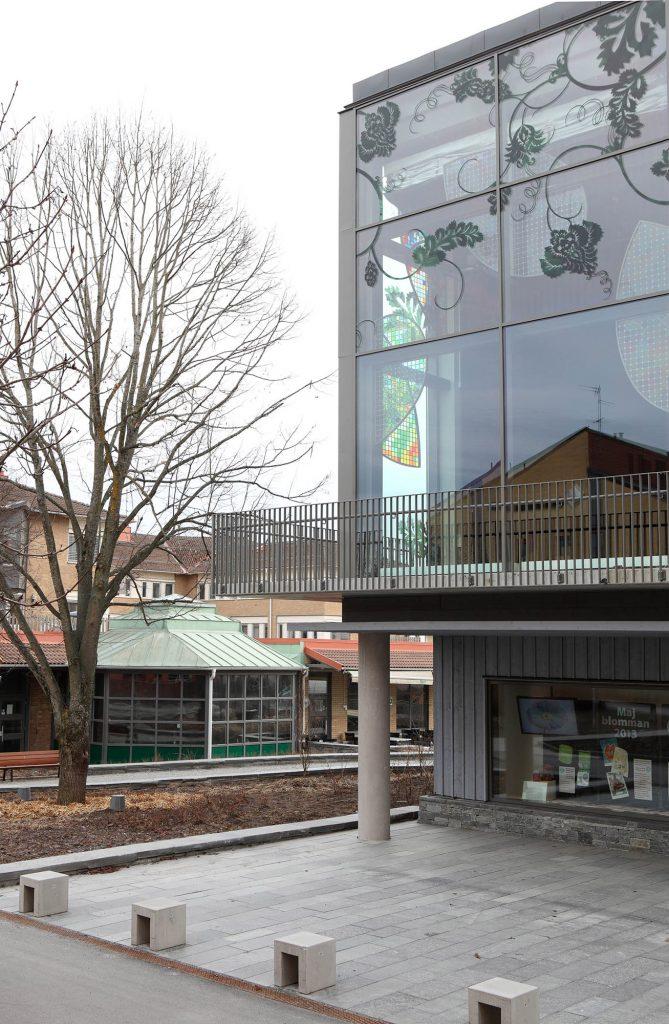 Vallentuna kulturhus utifrån, genom fönstret syns de färgade glasmosaikskärmarna. In Vitro, Kristoffer Zetterstrand