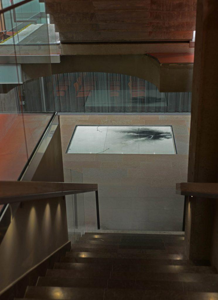 En trappa leder ner till den vita golvplattan med kol och två elsladdar. Nina Canell, Impulse Slight (100 000 Volt)