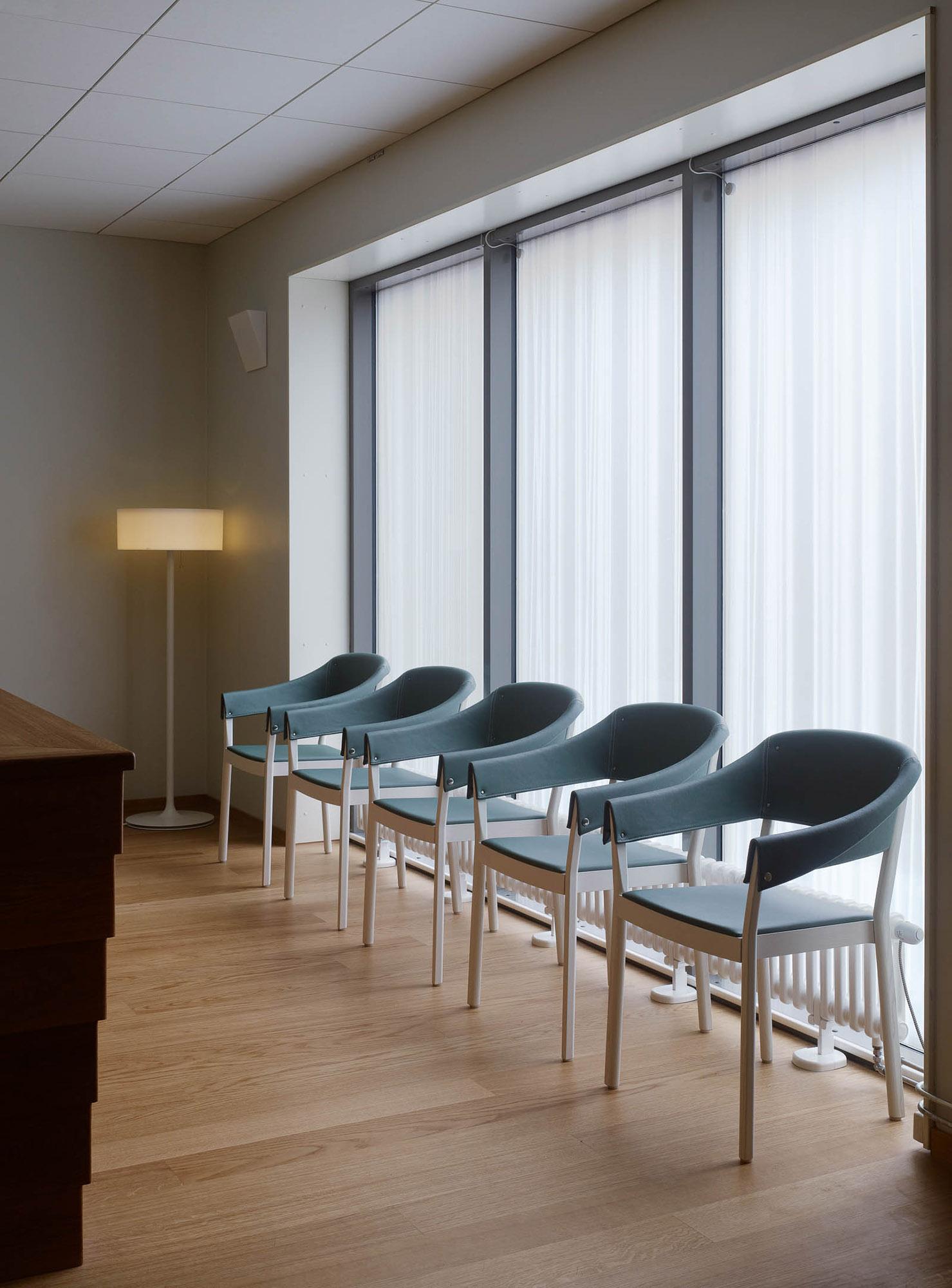 Gröna stolar längs väggen i avskedsrummet. Ingegerd Råman, Crystal Curtain (2013)