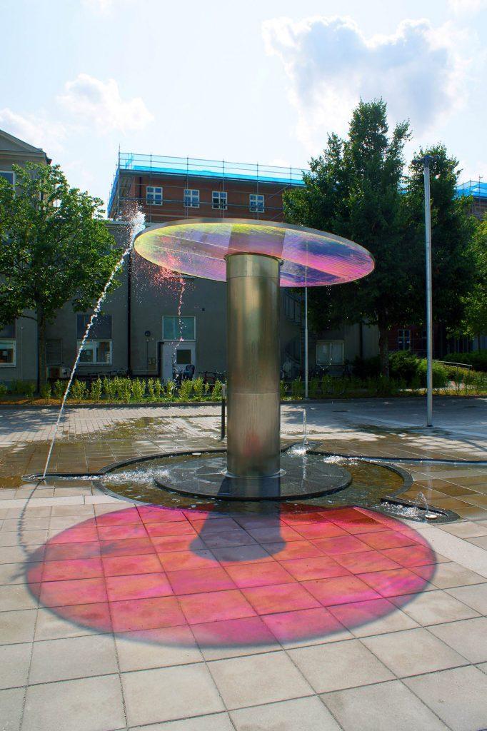 Fontän med horisontell glasskiva som reflekterar ett rödrosa ljus på marken under. Torbjörn Johansson, Källan Är, 2014