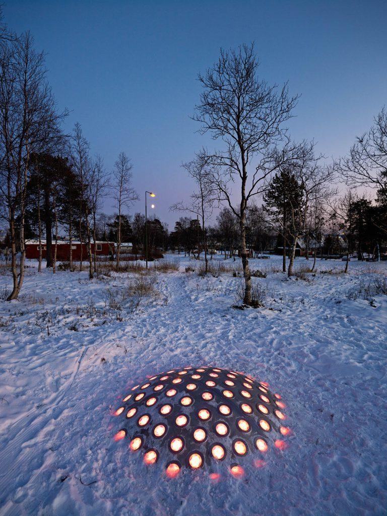 Ur den nedtrampade snön sticker stålkupolen upp vars lampor lyser orangea i halvmörkret. I bakgrunden träd och röda byggnader. Markus Lantto, Termonoder, 2009