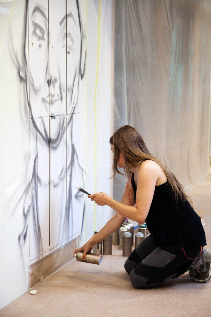 En kvinna sitter på huk och sprejar ett mänskligt ansikte på väggen. Pärra Andreasson, Vad Vi Vill