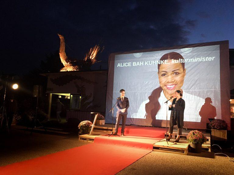 På en scen utanför Jordbro kultur och föreningshus. Per Sternbeck till vänster och Alice Bah Kuhnke till höger. Stor projektion i bakgrunden av Alice Bah Kuhnke.