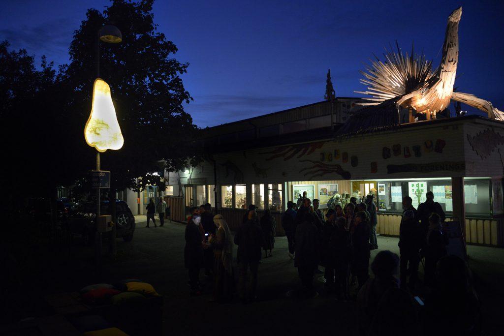 Människor i skymningen utanför kulturhuset i Jordbro, näsan på lyktstolpen är tänd och syns till vänster i bild, träskulpturen i form av en fågel står på kulturhusets tak till höger i bild.